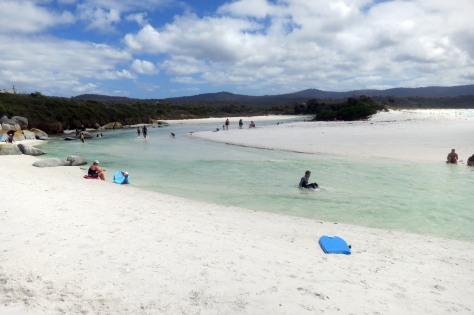 Families enjoying the natural whirlpool and sandbars of the Bay of Fires.