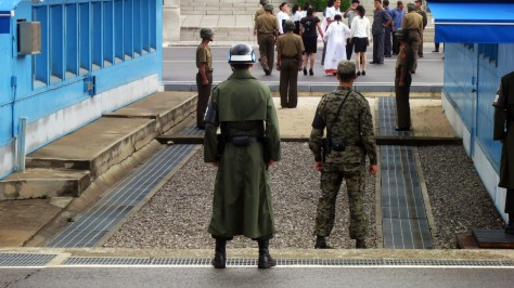 North Korean and South Korean soldiers dutifully guarding their respective sides of the border at the JSA.